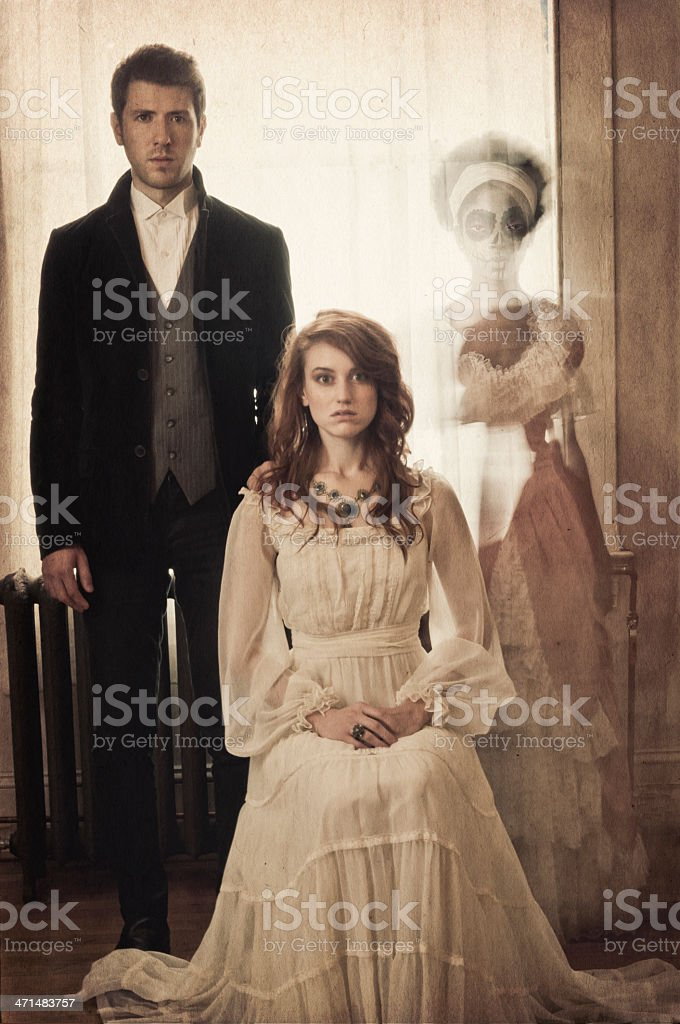 Vintage portrait of a young couple with ghostly apparation (II) stock photo