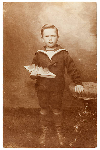 Vintage Portrait of Boy with Toy Boat Vintage sepia toned portrait of a young boy wearing a sailor's outfit holding a toy boat. Some dust and scratches which convey age of original image. Circa 1910. edwardian style stock pictures, royalty-free photos & images