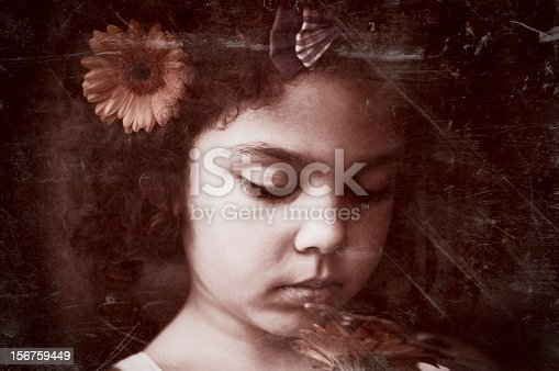 Royalty free stock photo of little girl holding a flower. Toned the image to sepia with addition of vignette and scratches to give a more vintage feel.