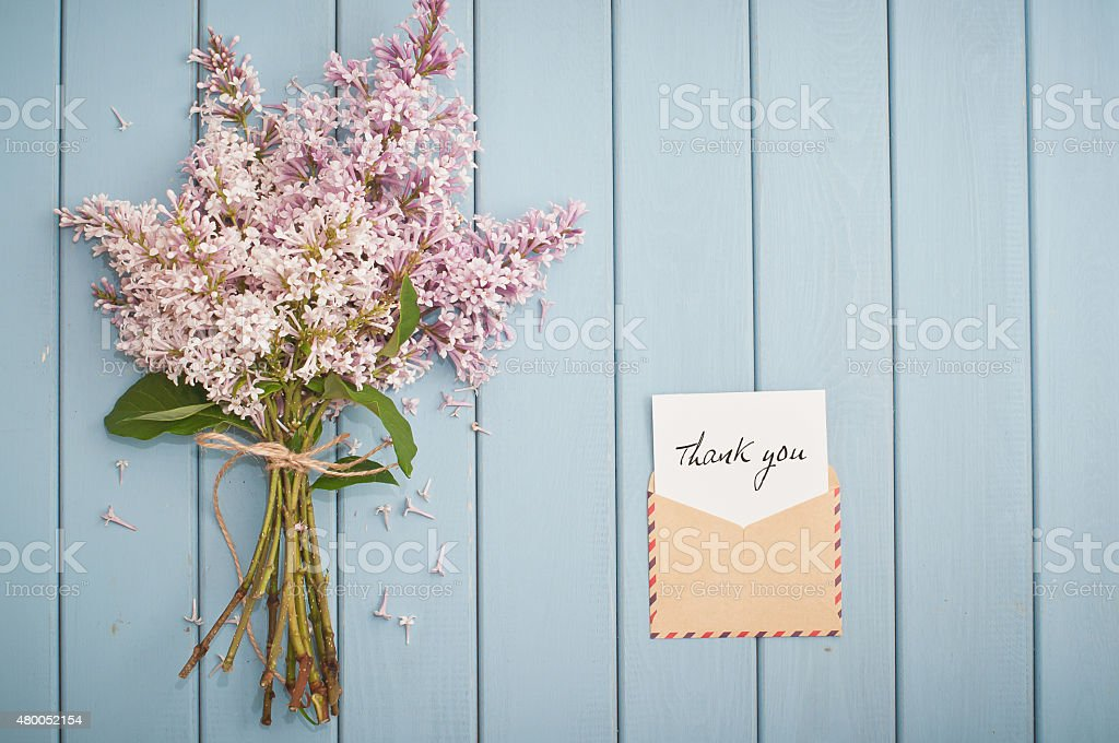 vintage postage envelope with card and summer bouquet of lilac stock photo