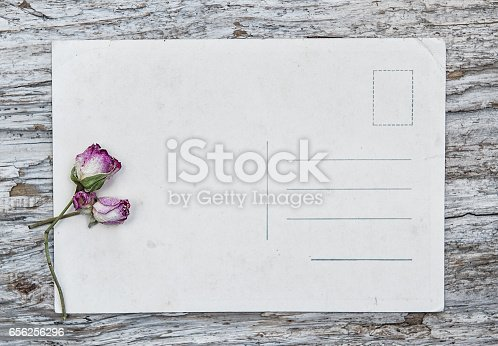 882302538 istock photo Vintage postcard and dry tea roses on the old wood 656256296