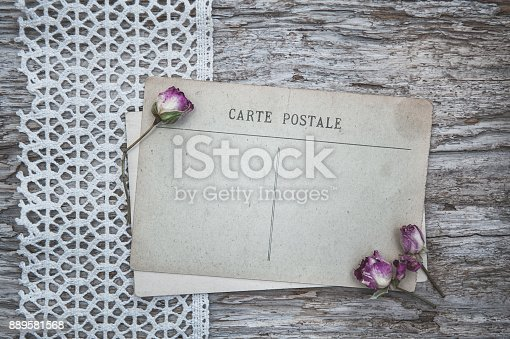 882302538 istock photo Vintage postcard, lace fabric and dry tea roses on the old wood 889581568
