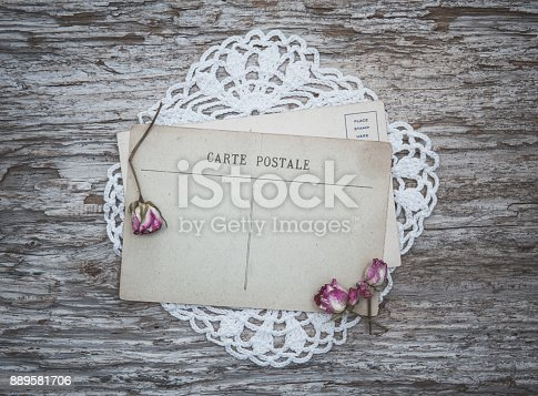 882302538 istock photo Vintage postcard, lace fabric and dry tea roses on the old wood 889581706