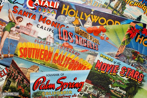 San Diego, CA, USA - February 27, 2018: A close up of several vintage postcards from the 1930's, 1940's and 1950's representing various cities and areas in the greater Los Angeles area rest randomly on top of each other in a studio setting. Cities and areas represented include Catalina Island, Los Angeles,Santa Monica, Hollywood, Pasadena, and Palm Springs.  The postcards were a popular way for visitors and travelers to share their travel experiences with friends and family during the mid-20th century.