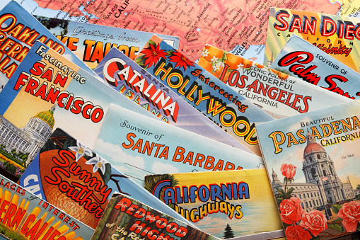 San Diego, CA, USA - February 27, 2018: A close up of several vintage postcards from the 1930's, 1940's and 1950's representing various cities and areas in California rest randomly on top of a map of California photographed in a studio setting. Cities and areas represented include Santa Barbara, San Diego, Los Angeles, San Francisco, Catalina Island, Hollywood, Pasadena, and Palm Springs.  The postcards were a popular way for visitors and travelers to share their travel experiences with friends and family during the mid-20th century.