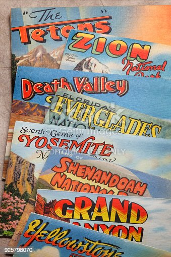 San Diego, CA, USA - February 27, 2018: A close up of several vintage postcards from the 1930's, 1940's and 1950's representing various U.S. National Parks rest randomly on top of each other while photographed in a studio setting. National parks represented include Zion, Grand Teton, Death Valley, Yosemite, Everglades, Grand Canyon, Shenandoah, and Yellowstone National Parks. The postcards were a popular way for visitors and travelers to share their travel experiences with friends and family during the mid-20th century.