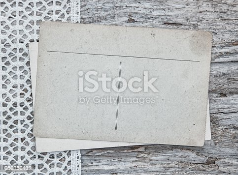 882302538 istock photo Vintage postcards on the lace and old wood 656256432