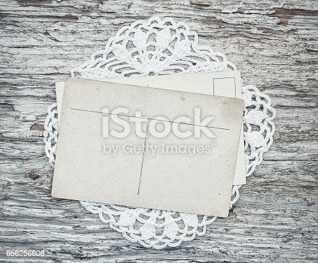882302538 istock photo Vintage postcards on the lace and old wood 656256608