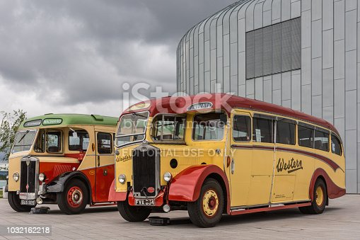 Glasgow, Scotland, UK - June 17, 2012: Along River Clyde, outside Riverside Museum, vintage yellow and red Western and Macbraynes public buses under heavy cloudscape.
