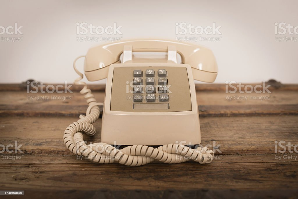 """Vintage Push Button Telephone on Old Wood Trunk """"Slightly desaturated color image of a vintage, push button telephone sitting on a wood trunk."""" 1970-1979 Stock Photo"""