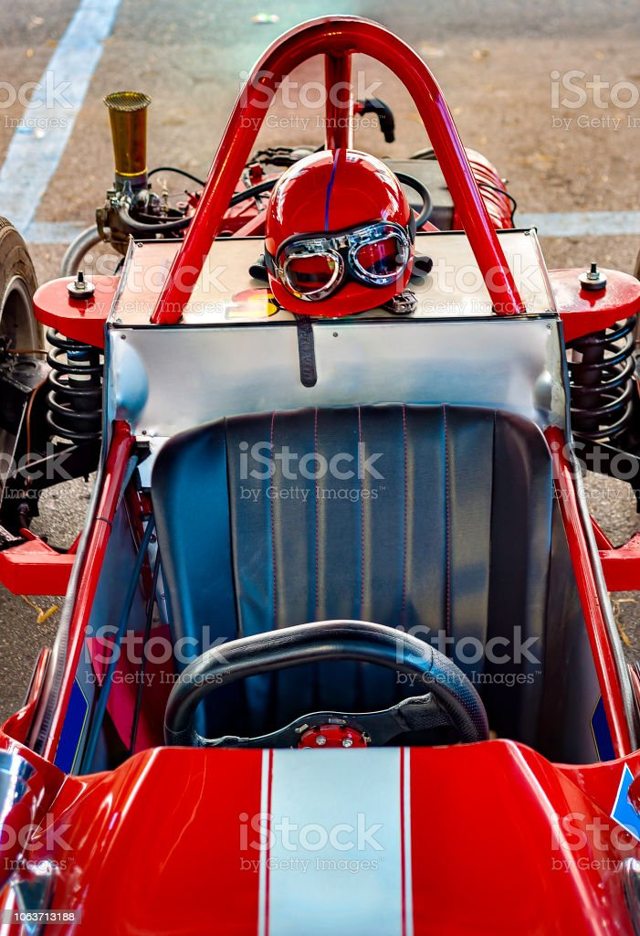 Vintage racing helmet and glasses resting on an antique sports car. stock photo