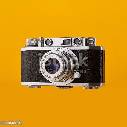 Vintage rangefinder film camera isolated on yellow / orange colored background