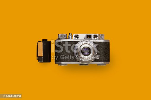 Vintage rangefinder film camera with a film canister isolated on yellow / orange colored background