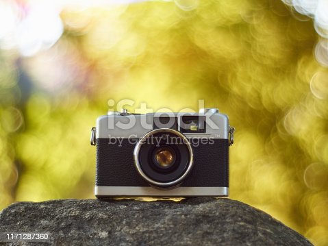 Vintage rangefinder film camera with glowing creamy bokeh at the background