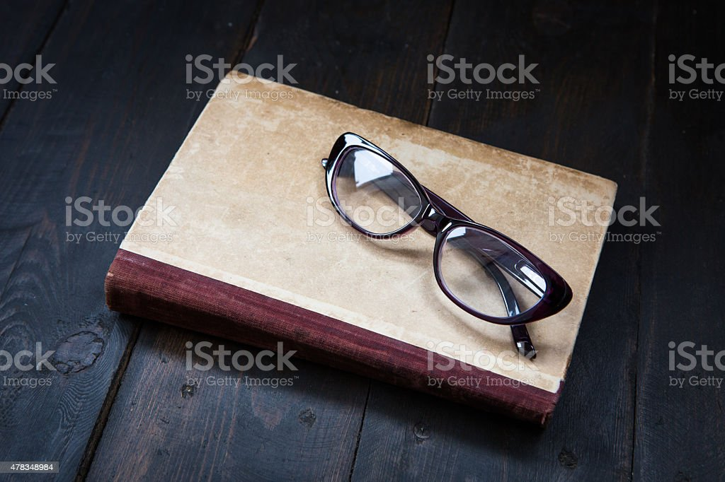 Vintage reading glasses on the book stock photo
