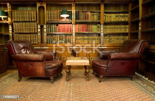 Old studying room with two leather armchairs and chess game
