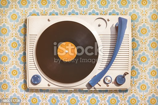 istock Vintage record player on top of flower wallpaper 480011708