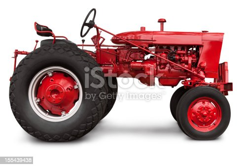 Isolated profile of a newly painted old red farm tractor - Precise clipping path provided. The image was cleaned up of grass and debris in Photoshop. Canon 5D MarkII.