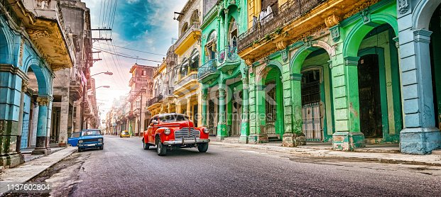 Vintage red oldtimer car driving through Havana Cuba