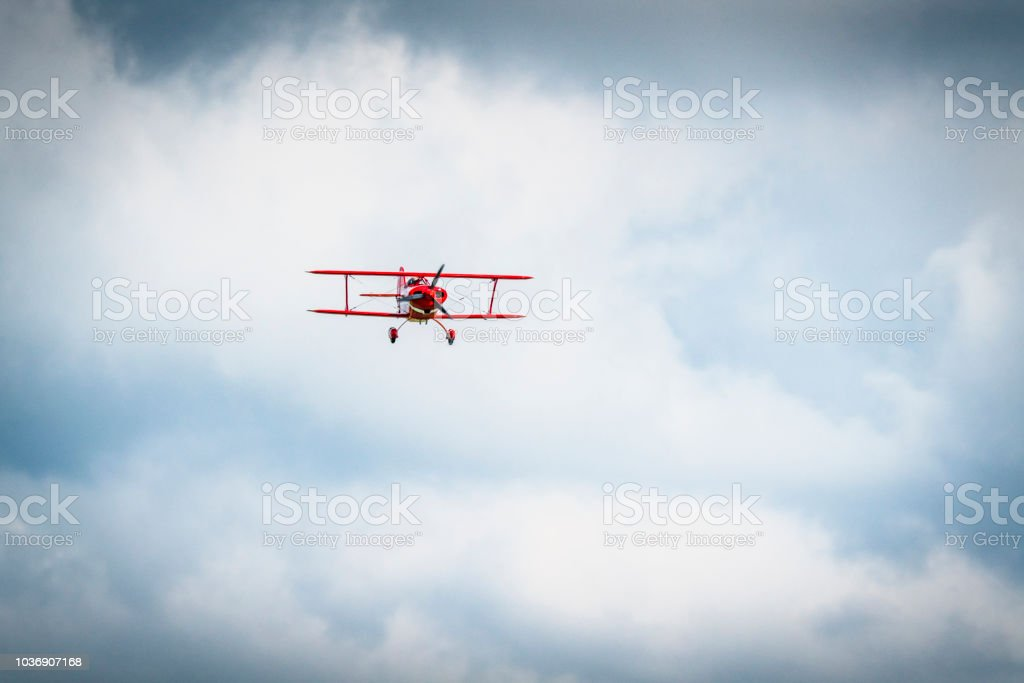 Vintage red propeller plane flying on a blue sky stock photo