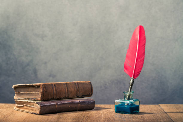 vintage red quill pen with inkwell and old books on wooden table front concrete wall background. retro instagram style filtered photo - cora��o imagens e fotografias de stock