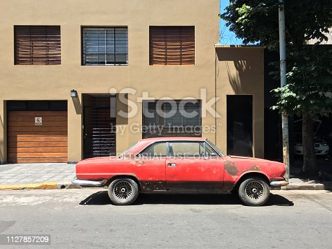Buenos Aires, Argentina - February 5, 2019: Vintage Torino sports car in bad condition parked in the street next to repair shop to the right. A lot of people buy this old cars in order to remodel them brand new