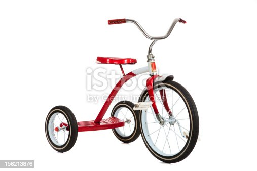 A red toy tricycle on a white background with copy space