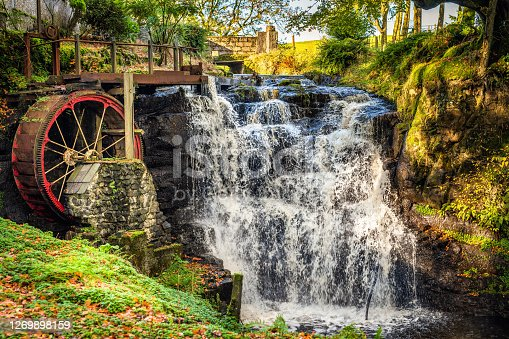 Vintage red waterwheel with waterfall in autumn colours in Glenariff Forest Park, Count Antrim, Northern Ireland