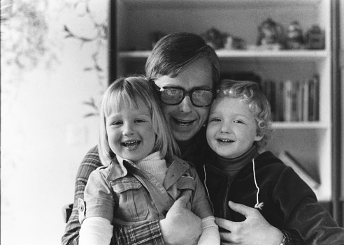 Vintage monochrome 1977 portrait of a happy father making funny faces with son and daughter.