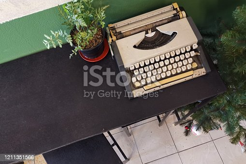 504606248 istock photo Vintage retro classic typewriter in cafe against wooden table. 1211351566
