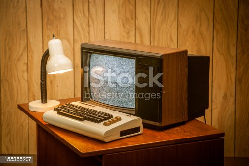 Product photo of an old commodore vic-20 vintage retro computer on wood desk, an 80's lamp and wood panelling in the back.