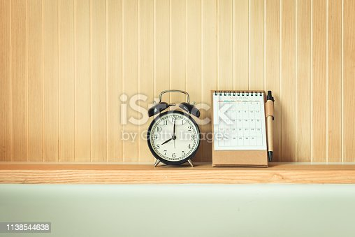 istock Vintage Retro of Alarm Clock and Calendar on Headboard Shelf, Interior Bedroom and Decorative Design. Black Timer Clock is Layout Against on Isolate Stripes of Wooden Background. Travel Annual Leave. 1138544638