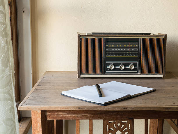 vintage retro radio, notebook and pen on wooden table stock photo