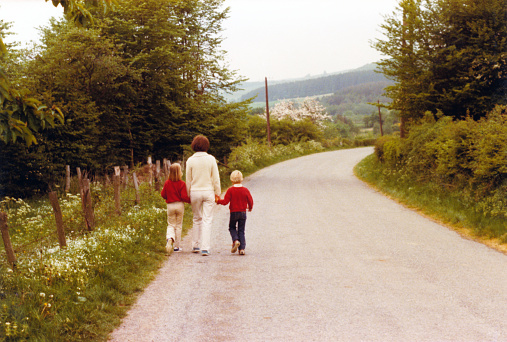 Vintage 1979 image of a young mother walking hand in hand on the side of the road with her daughter and son.
