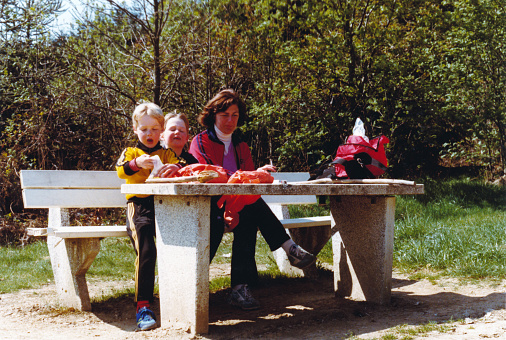 Vintage colorful 1979 roadtrip image of a young mother with son and daughter sitting at picnic table and eating a sandwich on a parking on the German highway.