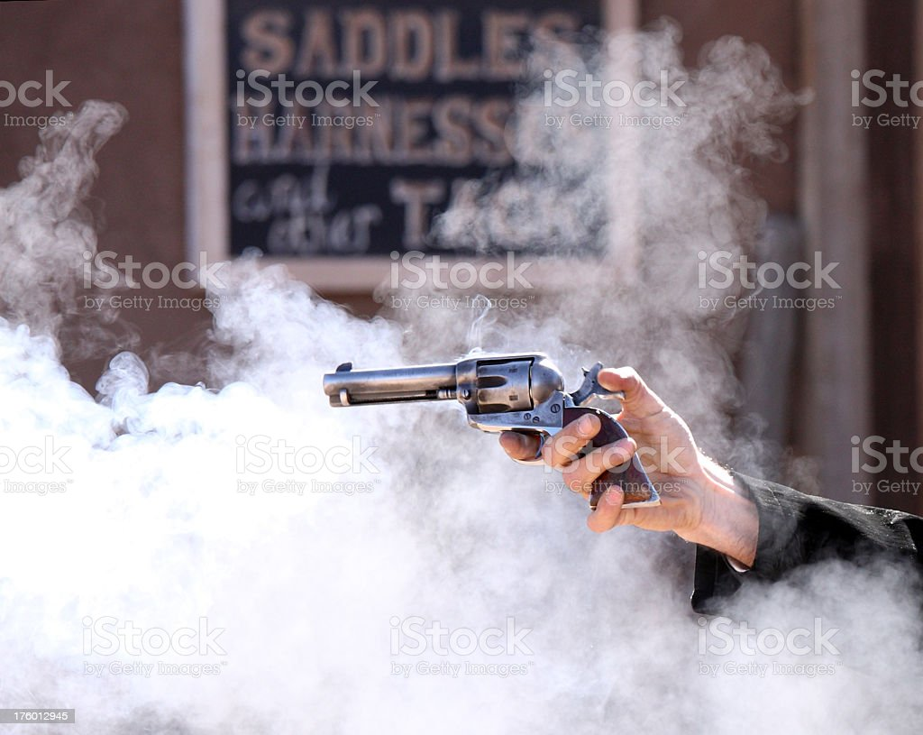 Vintage revolver fire arm surrounded by smoke clouds stock photo
