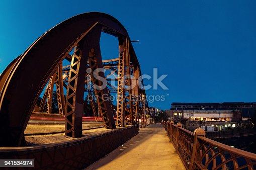 Vintage river bridge and industrial building at night