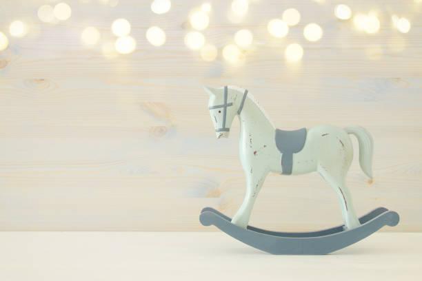 vintage schaukelpferd auf holzboden. glitzer-overlay - pferde schlafzimmer stock-fotos und bilder