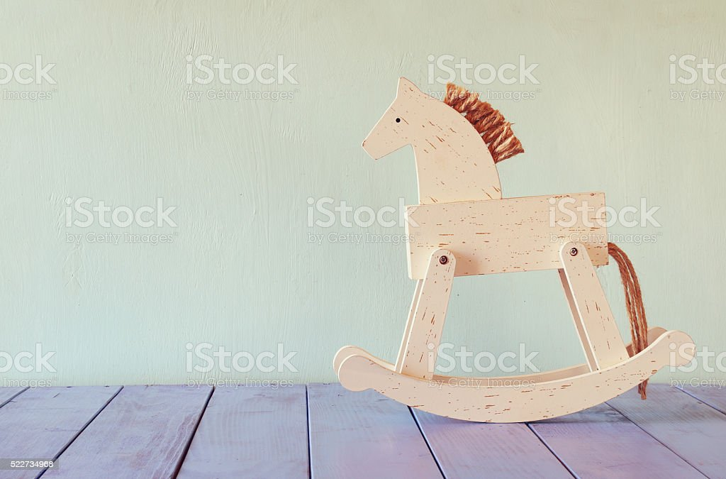 vintage rocking horse on wooden floor. retro filtered image stock photo