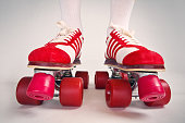 A pair of vintage red and white tennis shoe roller skates.