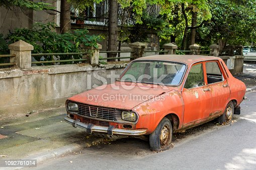 Abandoned red vintage Romanian Dacia 1300 with flat tires