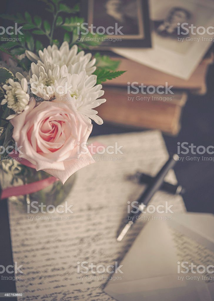 Vintage rose bouquet with love letter, pen, books and photos stock photo