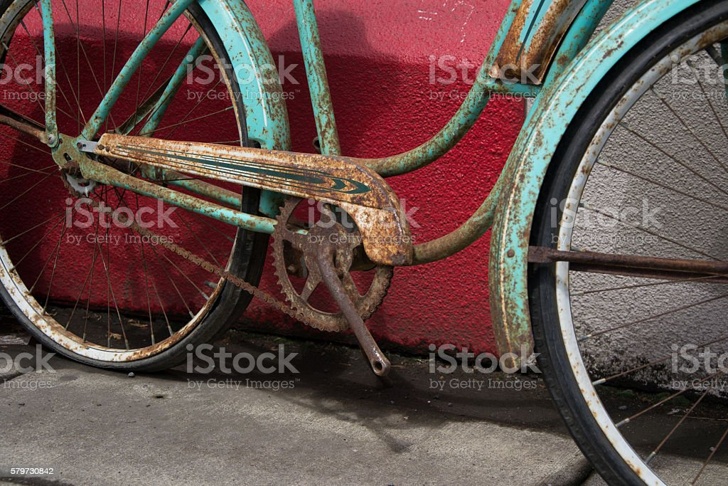 Vintage rusty bike without pedals over a red wall - Photo