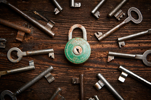 istock Vintage rusty padlock surrounded by old keys 614219412