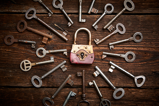 istock Vintage rusty padlock surrounded by old keys 614221210