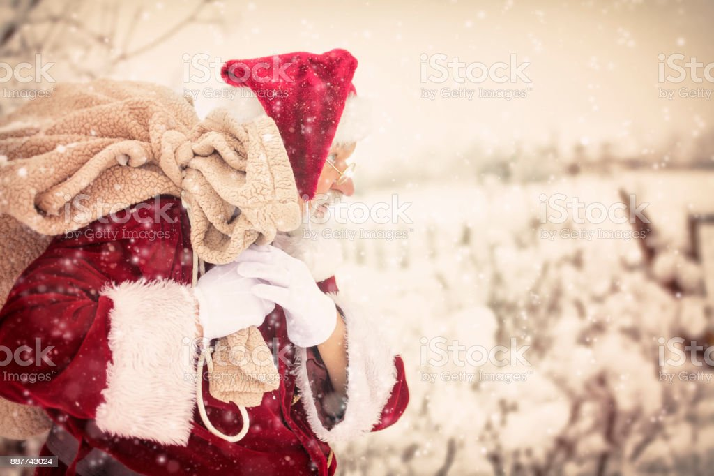 Vintage Santa Carrying His Pack Of Toys In A Winter Storm stock photo