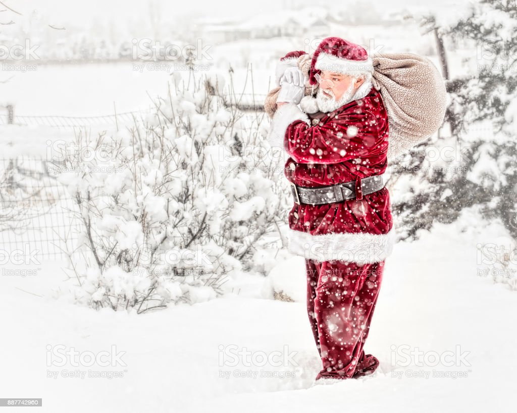 Vintage Santa With Toy Pack On His Back Outdoors In A Snow Storm stock photo
