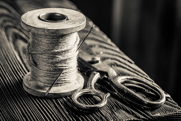 vintage scissors and threads on spools - sewing machine needle stock photos and pictures