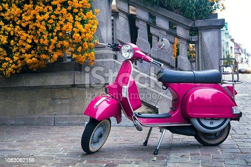 Vintage purple motor scooter on the city street in Belgium.
