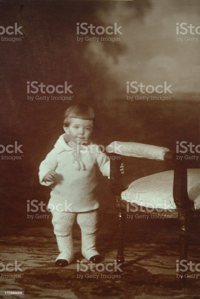 Vintage sepia photo of little boy at chair royalty-free stock photo